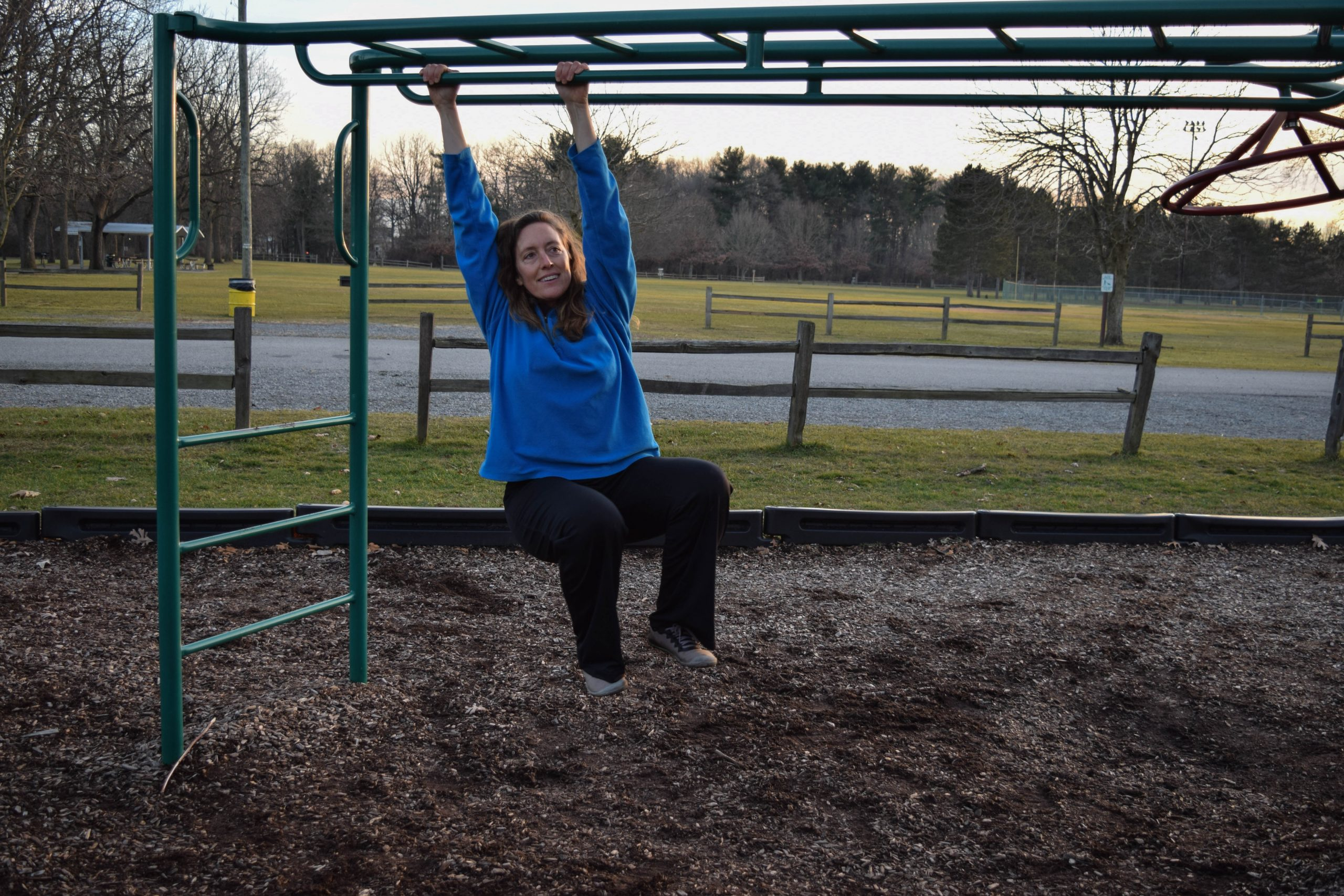 Linda hanging on the monkey bars